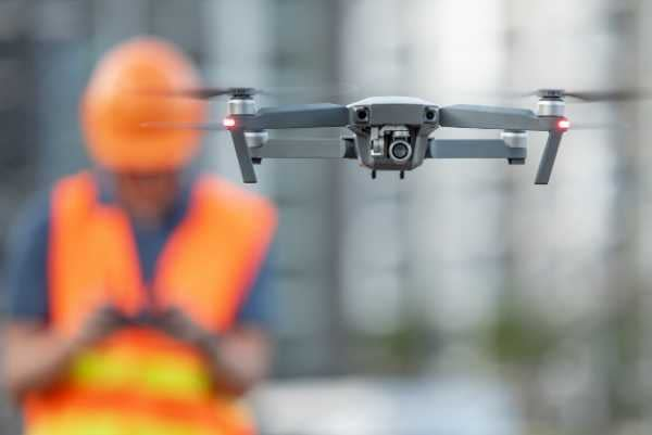 a construction worker piloting a drone remotely