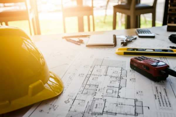 hard hat and architectural plans on construction site